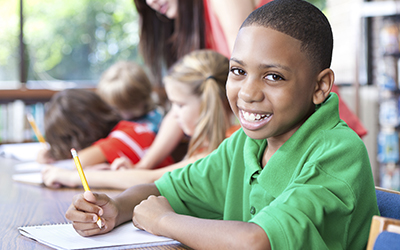 Young boy in classroom writing and smiling